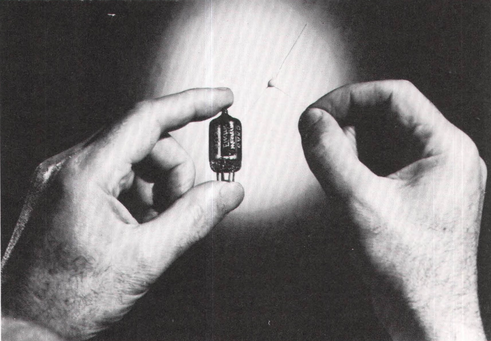 A production version of the transistor is shown at right, next to a vacuum tube.