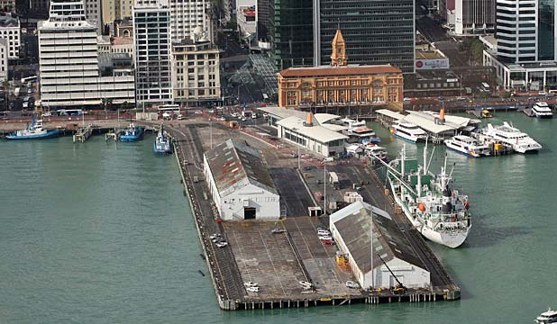 This image of two warehouses on the waterfront captures the stages of construction of Queen's Wharf