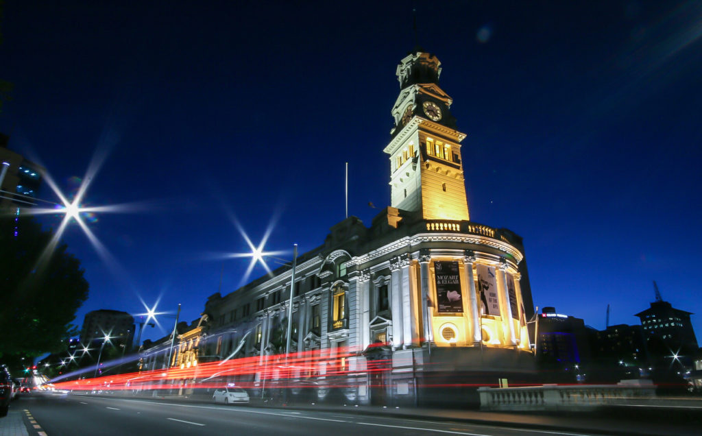 A photograph of a rectangular, white stone government building with a clock tower, sitting on the corner of a city block in Auckland. It is night so the sky is a dark blue and there are lights on the sides of the building illuminating its walls.